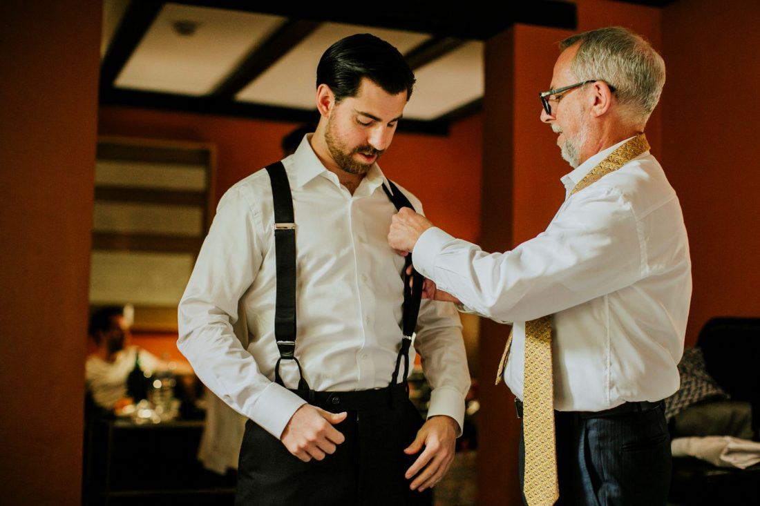 The groom being helped by his Dad.
